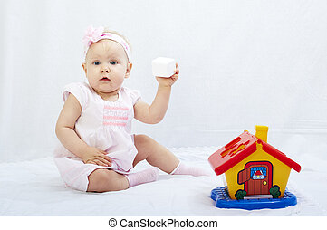 baby is playing with toys over white background