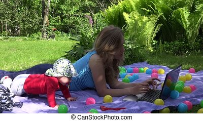 Baby kid interrupt loving mother work with computer on plaid in garden. 4K