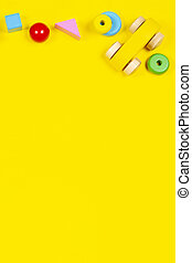 Baby kids toys background. Toy wooden car and colorful blocks on yellow background. Top view, flat lay