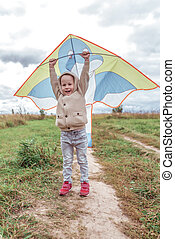 baby laughing. In hand is kite. Little boy 3-5 years old, autumn field background, emotions joy fun laughter fun pleasure happiness. Knitted warm sweater with hood. Playing airplanes flying a kite.