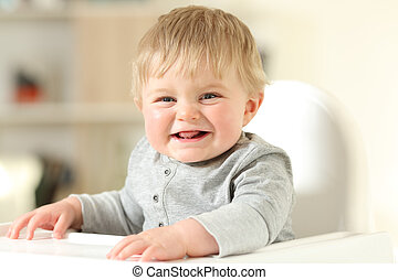 Baby laughing looking at camera on a chair