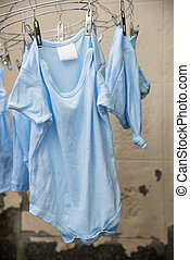 Baby laundry hanging on a clothesline and cement wall