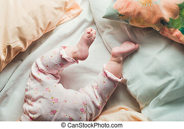 Baby legs in the bed