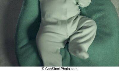 Baby lies on bed and crying. Mom gives him a dummy and strokes his cheeks.