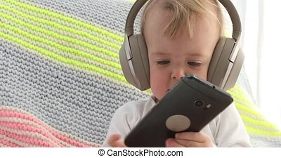 Baby listens headphones holding smartphone - One year old...