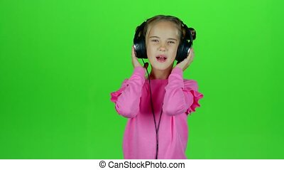 Baby listens to the music in the headphones. Green screen -...