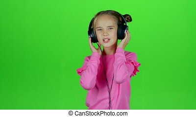 Baby listens to the music in the headphones. Green screen. Slow motion