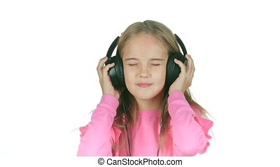 Baby listens to the music in the headphones. White...