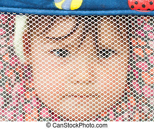 One year old half Chinese half caucasian baby hanging in a play pen looking through mesh.