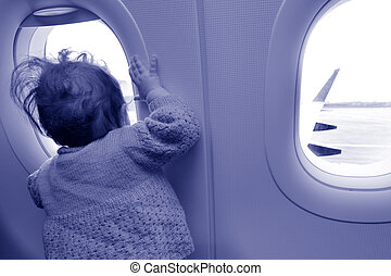 Baby looks out from airplane window