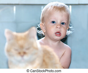 baby looks out from behind a red cat and looks directly at the camera