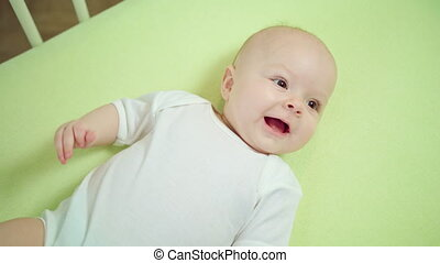 Baby Lying in a Crib at Home and Smiling