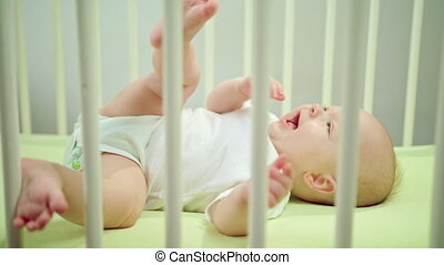 Baby Lying in a Crib at Home Eating its Fingers - Baby's...