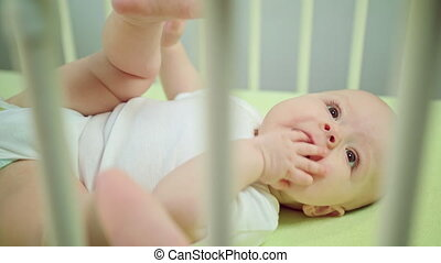 Baby Lying in a Crib Eating its Fingers - Baby's lying on a...
