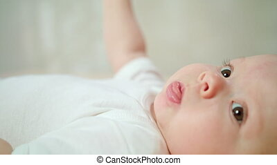 Baby Lying in Bed at HomeEating its Finger and Yawning