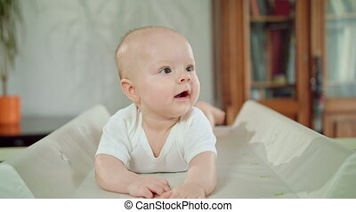 Baby Lying in Bed on its Belly at Home. Mouth Open