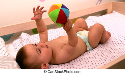 Baby lying in crib holding toy in slow motion