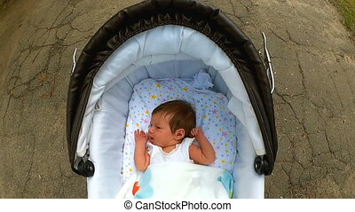 Baby lying in the pram and smiling - LIttle cute baby in...