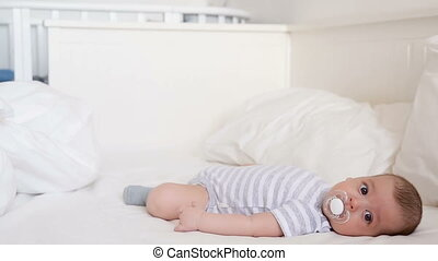 baby lying on a large bed with a pacifier