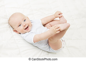Baby Lying on Back, Happy Smiling Kid Holding Legs in Hands, Newborn Child Lie on White Background and looking at camera