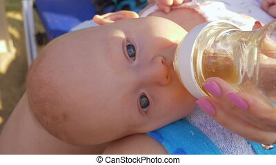 Baby lying on mothers lap and drinking from the bottle