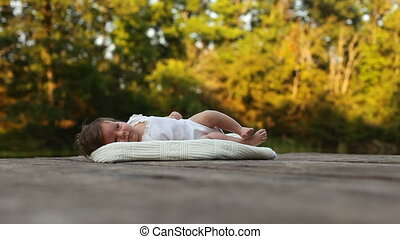 Baby lying on the blanket in the forest