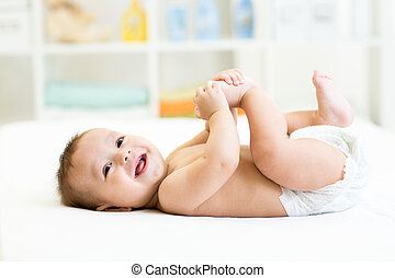 0d36fc9da Baby lying on back smiling with feet in the air. Portrait of a cute ...
