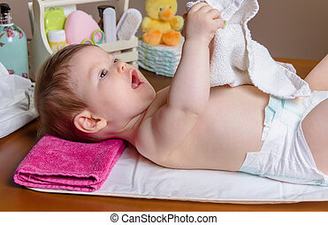 Baby lying playing with a small towel
