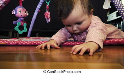 A sweet baby is attempting to crawl from a low angle cinematic shot.