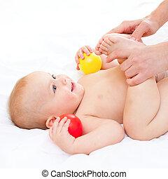 Mother massaging her little baby girl, shallow focus