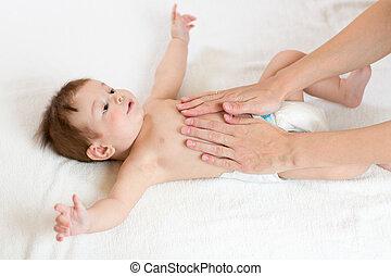Baby massage. Mother massaging infant belly