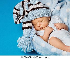 baby newborn portrait, kid sleeping in hat on blue background