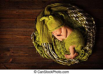 baby newborn portrait, kid sleeping in woolen hat on brown wooden background