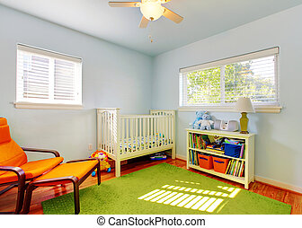 Baby nursery room design with green rug, blue walls and...