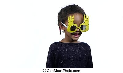 Baby of an african american girl dancing in funny glasses. White background. Slow motion