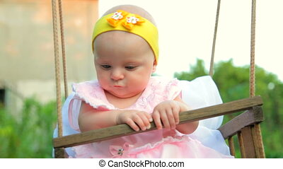 Baby on a swing at backyard