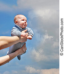 baby on father's hands over sky background