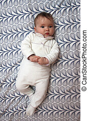 baby on pattern background - Cute baby laying on back on ...