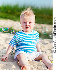 Baby on the beach playing with soap bubbles