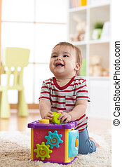 baby parvel, leka, inomhus, med, sorterare, leksak, sittande, på, mjuk, matta