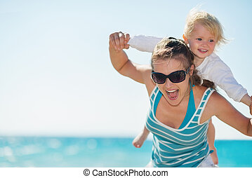 Baby piggybacking mother on beach
