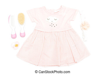 Baby pink dress and care items on a white background. Flat lay