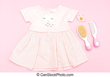 Baby pink dress for a girl and care items on a pink background. Flat lay