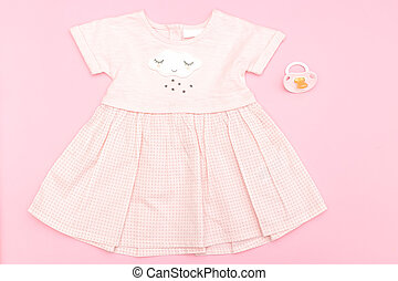 Baby pink dress for a girl on a pink background. Flat lay