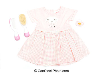Baby pink dress on a girl and care items on a white background. Flat lay