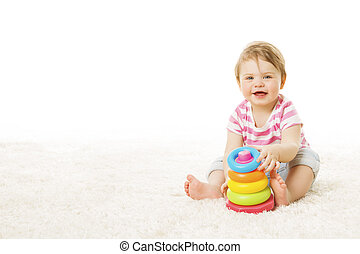 Baby Play Toy Rings Pyramid, Infant Kid Playing Building Blocks, one year Child Sitting on Carpet over White Background
