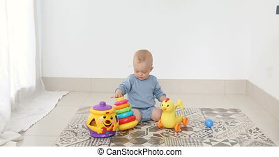 Baby play with pyramid - Toddler boy playing with a toy...