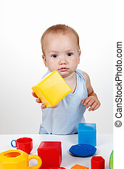 Baby play with toy cube in blue dress smiling