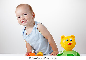 Baby play with toy in blue dress smiling