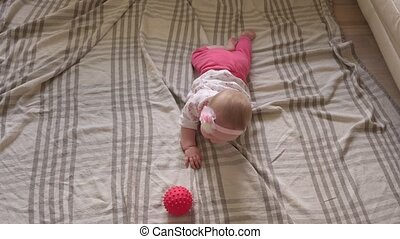 Baby playing and learning to crawl on floor at home, top ...